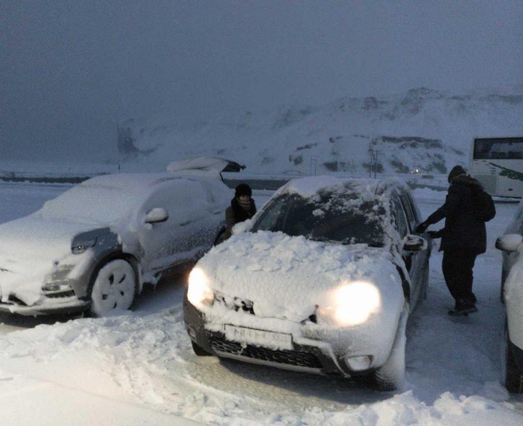 quitando nieve del coche en Islandia